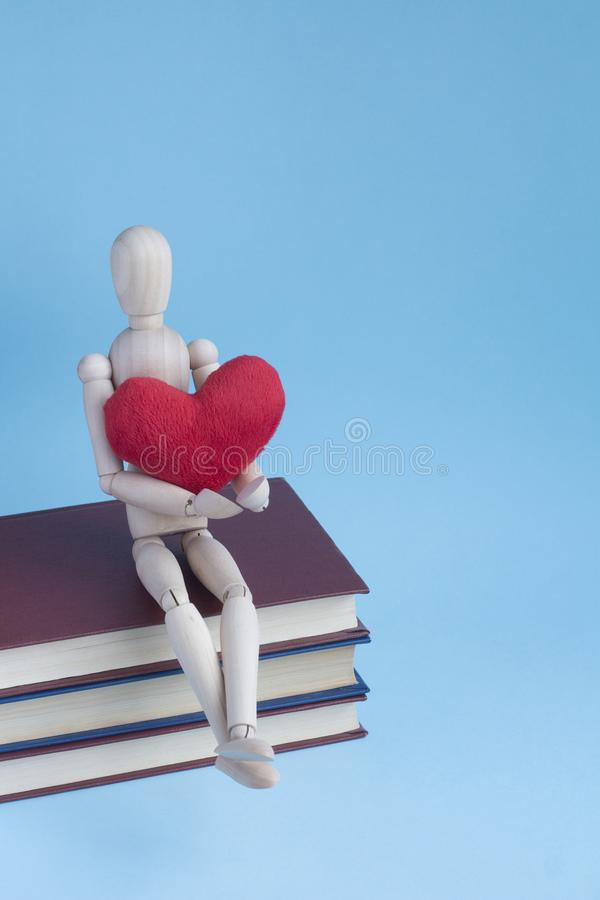 Wooden puppet human siting on a pile of books with red plush heart in hands.  stock photo