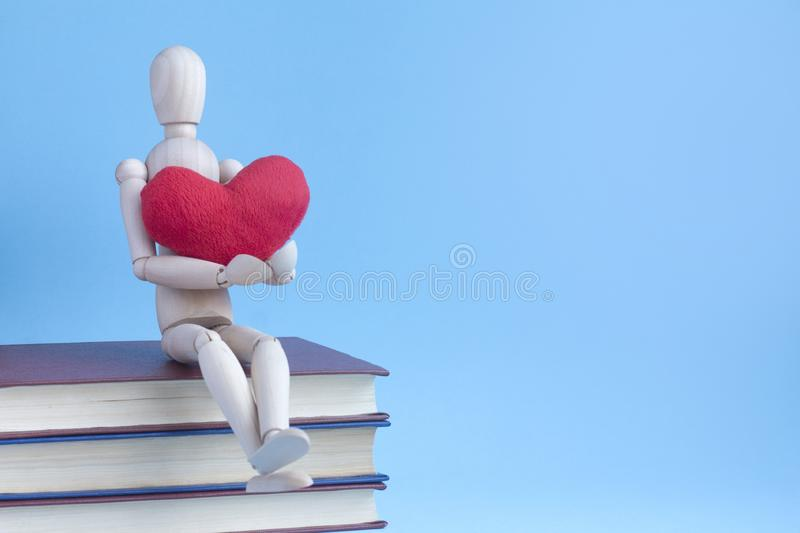 Wooden puppet human siting on a pile of books with red plush heart in hands.  royalty free stock image