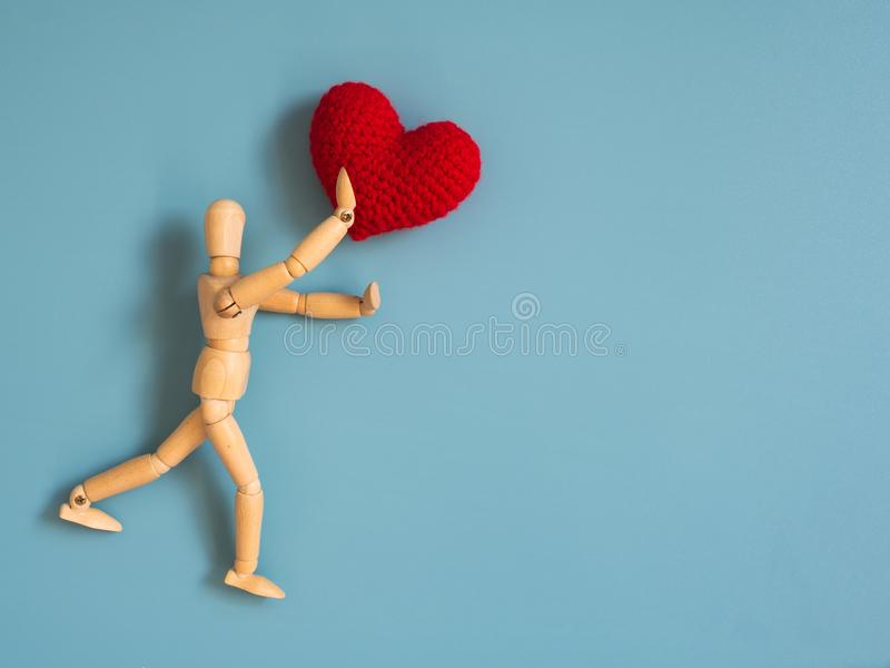 Wooden puppet jumping from the wooden floor in the air to catch the red heart floating in the sky. Wooden puppet try to jump to ca. Tch love. Concept of effort stock photos