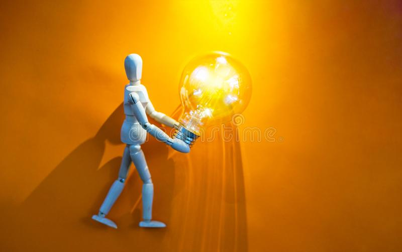 Wooden puppet with light bulb. In orange background.Wooden mannequin figure taking the first step to his goal- career, growth or development concept royalty free stock image