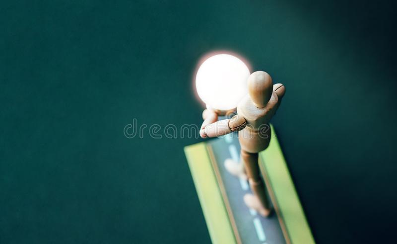 Wooden puppet with light bulb. Business Creative and Idea Concept.Idea and inspiration concept. Wooden mannequin holding glowing light bulb with empty space royalty free stock photos
