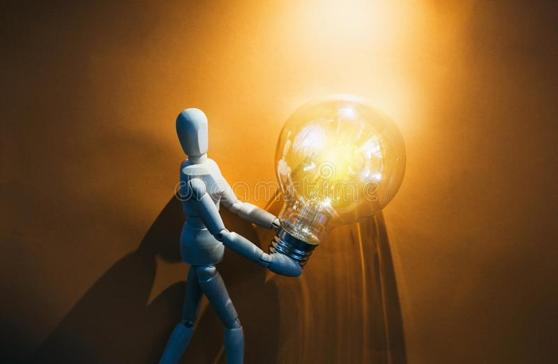 Wooden puppet with light bulb. In orange background.Wooden mannequin figure taking the first step to his goal- career, growth or development concept stock image