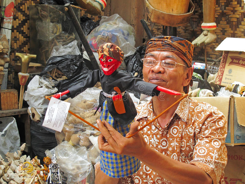 Wooden puppet maker. In Bandung, Indonesia. Wayang golek are wooden doll puppets that are operated from below by rods connected to the hands and a central royalty free stock photo