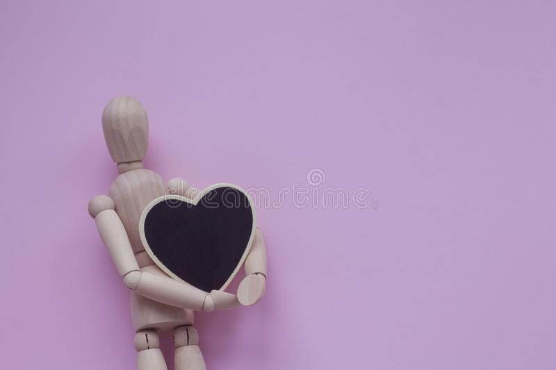 Wooden puppet man on a pink background holding black chalkboard heart.  royalty free stock photo
