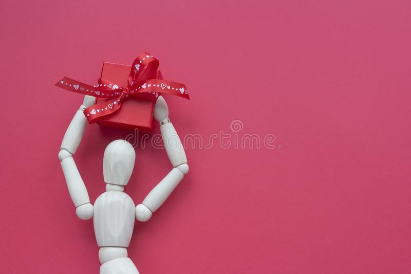 Wooden puppet man on red background holding romantic gift box over the head.  royalty free stock photo