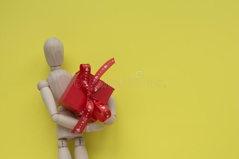 Wooden puppet man on yellow background holding red romantic gift box.  stock photo