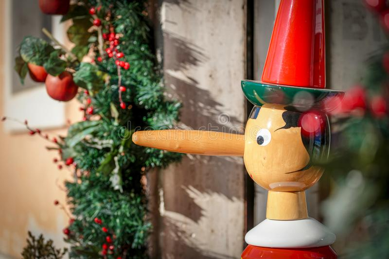 Wooden puppet of Pinocchio. A wooden puppet of Pinocchio in a street by x-mas time royalty free stock photo