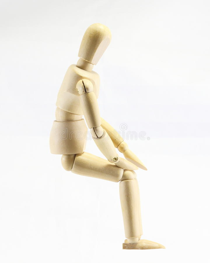Wooden puppet. Sitting pose hand on lap royalty free stock photos