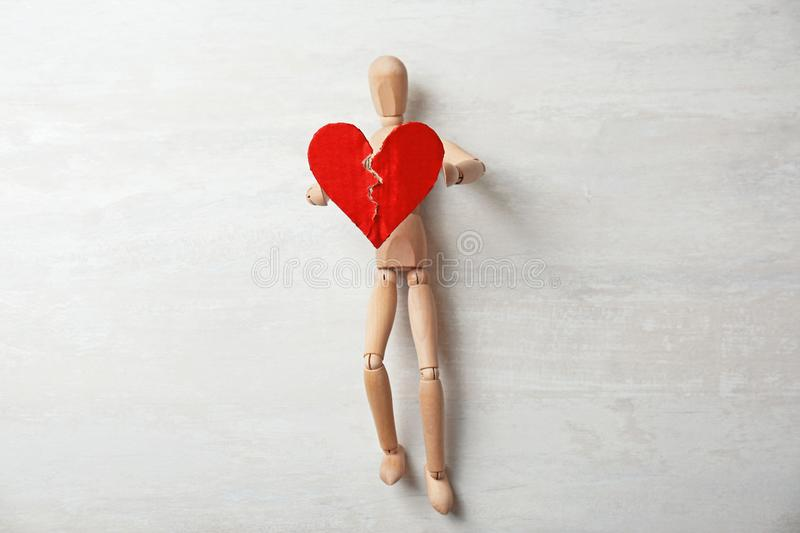Wooden puppet with torn cardboard heart on gray background royalty free stock image