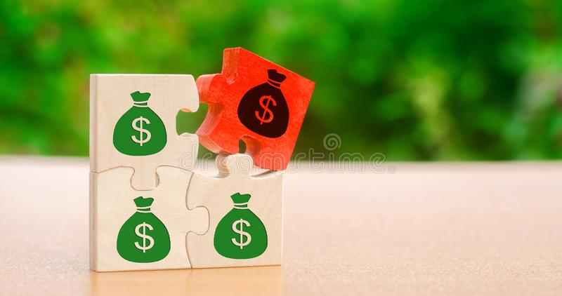 Wooden puzzles with the image of money. Withholding money and commission. Tax and taxation. The taxes burden. Net income. Costs. Ebitda. Business and Finance royalty free stock photography