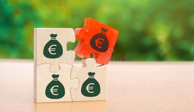 Wooden puzzles with the image of money. Withholding money and commission. Tax and taxation. The taxes burden. Net income. Costs. Ebitda. Business and Finance stock photos
