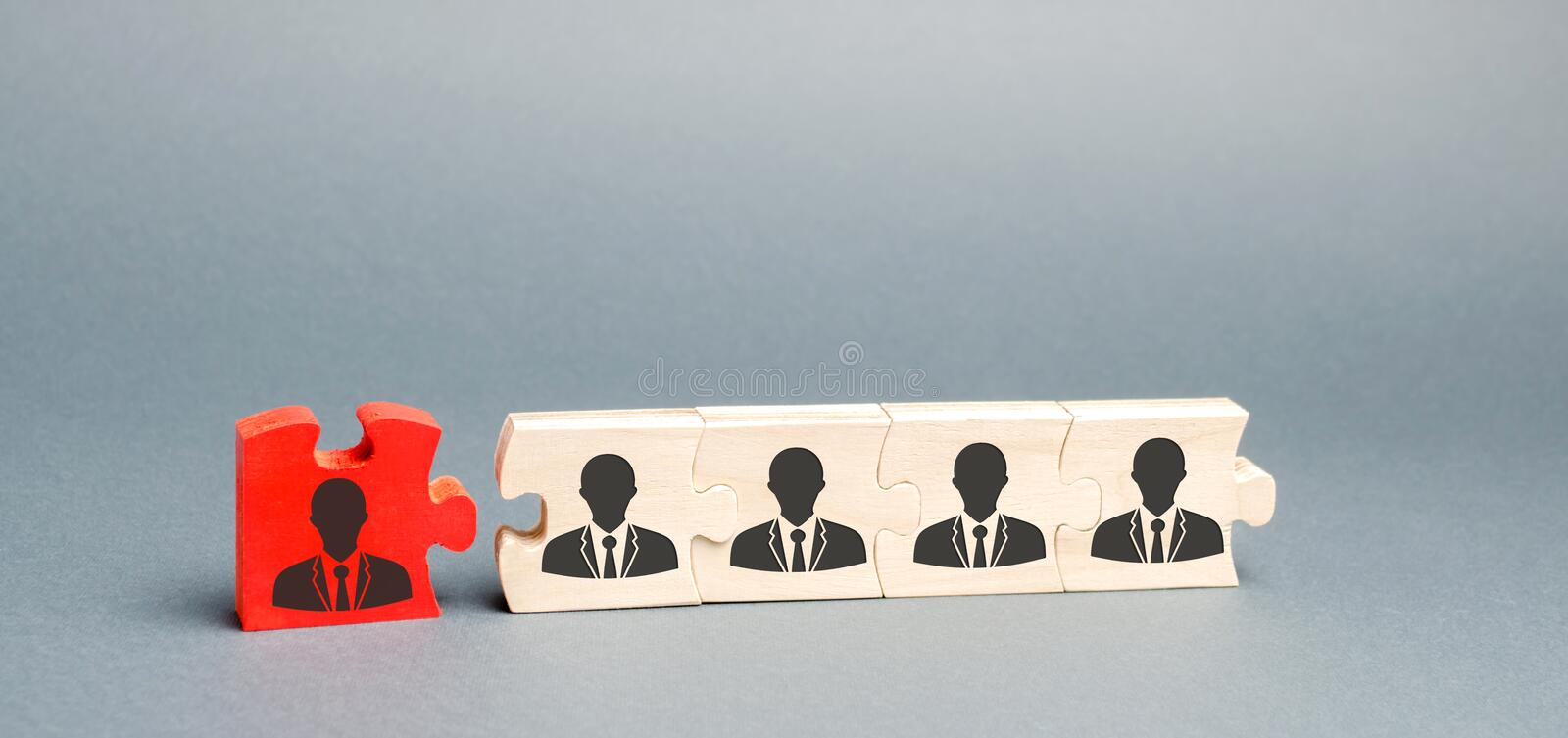 Wooden puzzles with the image of workers. The concept of personnel management in the company. Dismissing an employees from a team. Demotion. Bad worker. Staff stock images