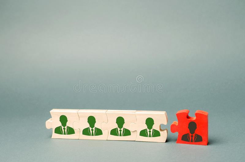 Wooden puzzles with the image of workers. The concept of personnel management in the company. Dismissing an employees from a team. Demotion. Bad worker. Staff royalty free stock photo