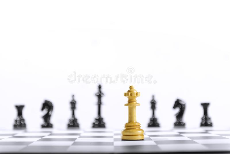 Wooden queen chess piece standing in front of whole group of black chess pieces. On the chessboard royalty free stock photo