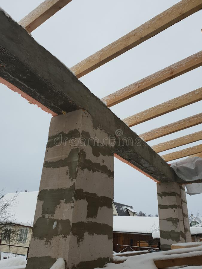 Wooden rafters lie on concrete beams, which are based on columns of foam blocks. Preparation of the working space of the house. Wooden rafters  on concrete royalty free stock photo