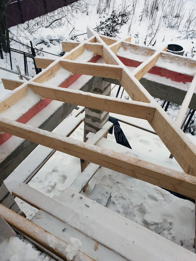 Wooden rafters lie on concrete beams, which are based on columns of foam blocks. Preparation of the working space of the house. Under construction for roof royalty free stock images