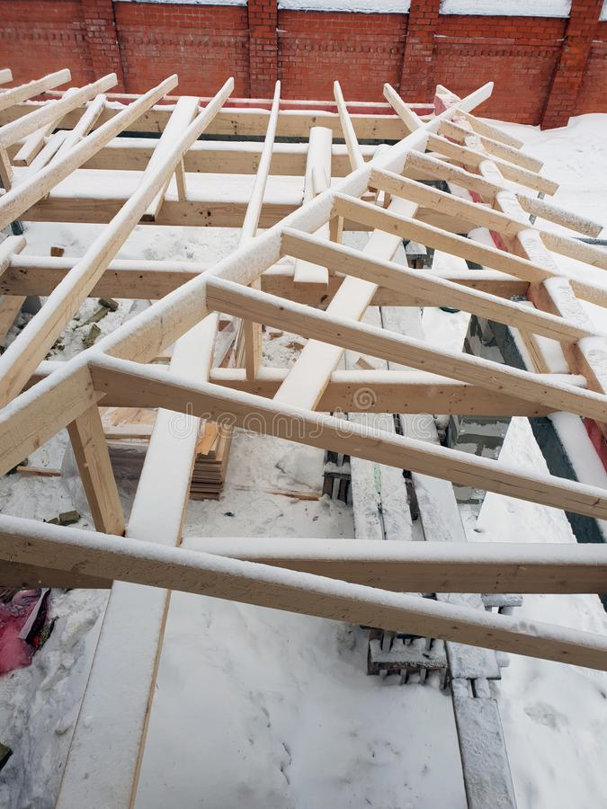 Wooden rafters lie on concrete beams, which are based on columns of foam blocks. Preparation of the working space of the house. Under construction for roof stock images