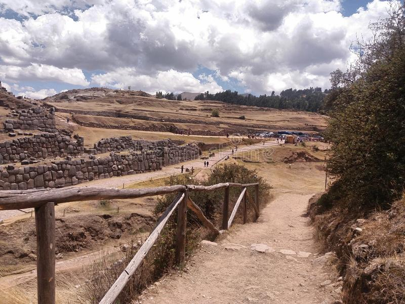 Wooden railing and dirt road. Wooden railing, dirt road, distant mountains blue sky with white clouds background, location cusco, peru royalty free stock photos