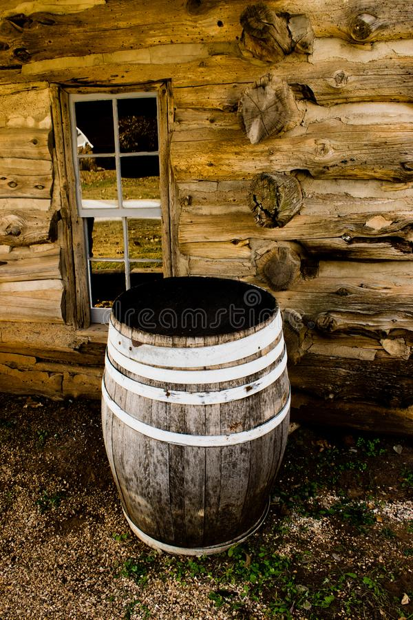Wooden Rain Barrel. In front of an old pioneer log cabin used to catch rain water for drinking, washing, and watering gardens royalty free stock photo