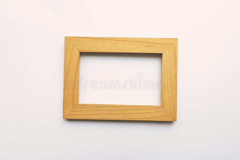 Wooden rectangular photo frame on white background. Close-up. Top view. Nobody, empty royalty free illustration