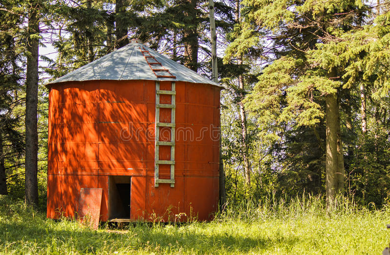 A wooden red grain bin. A red wood grain bin in front of some trees royalty free stock photo
