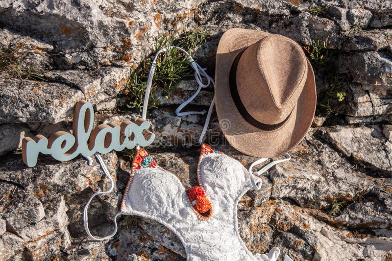 Wooden relax text a hat and a swimsuit on a rock stock photo