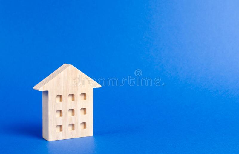 A wooden residential building stands on a blue background. The concept of buying and selling real estate, renting. Search for a house. Affordable housing royalty free stock photography