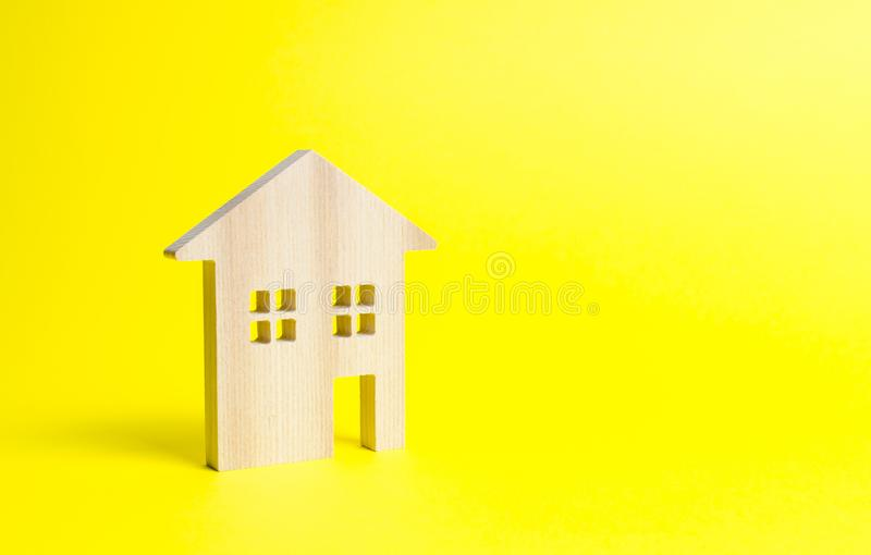 Wooden residential house on a yellow background. Mortgage and credit for the purchase. Minimalism. Isolate Real estate concept. Buying affordable housing stock image