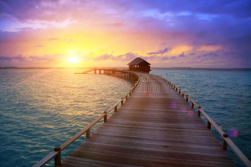 Wooden road from the island to a hut over water on a sunset. Maldives stock photo