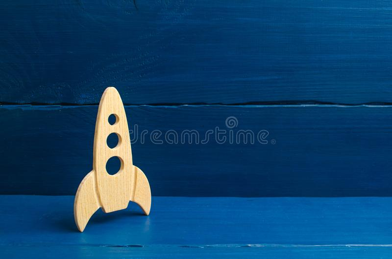 A wooden rocket on a blue background. The style is retro. The concept of space flights and achievements in high technologies. Busi. Ness take off and grow. Space royalty free stock image