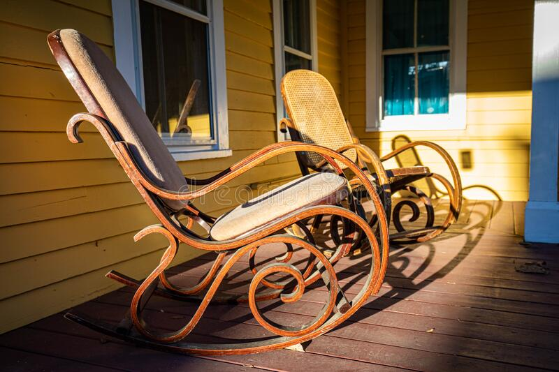 Wooden rocking chair on front porch at sunset. Nobody stock photography