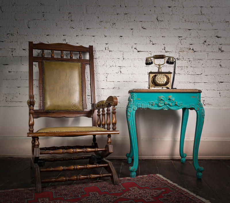 Wooden rocking chair, green vintage table and old telephone set stock photos