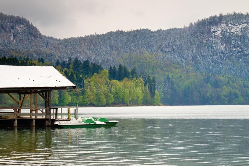 Wooden roof for trip holiday paddle boats. Holiday resort. On the shores of beautiful Alpine lake stock photography