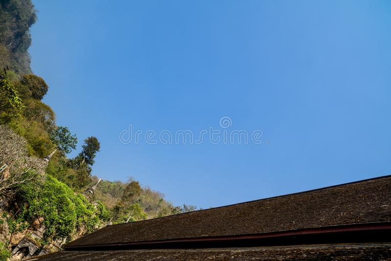 Wooden rooftop of an ancient Buddhist temple with clear blue sky background. royalty free stock images