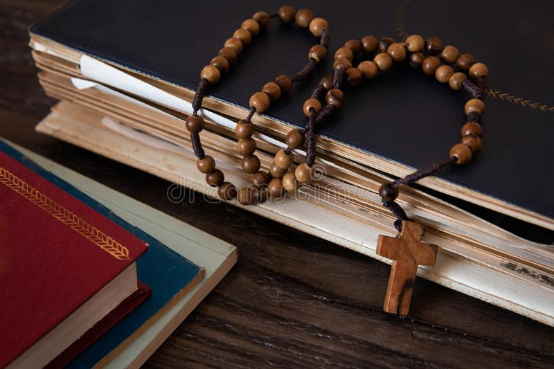 Wooden rosary beads on old books. Wooden background stock photos