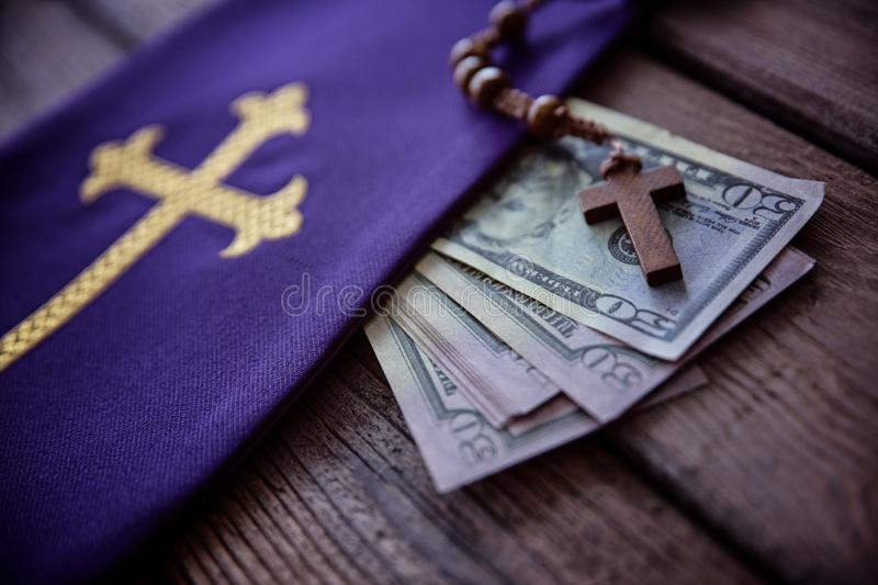 Wooden rosary and catholic church symbols and money. Church and money royalty free stock photography