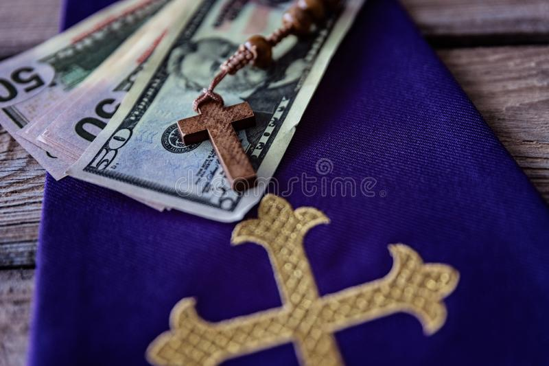 Wooden rosary and catholic church symbols and money. Church and money royalty free stock images