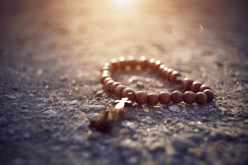 Wooden rosary with a cross lie on a rocky surface royalty free stock photos