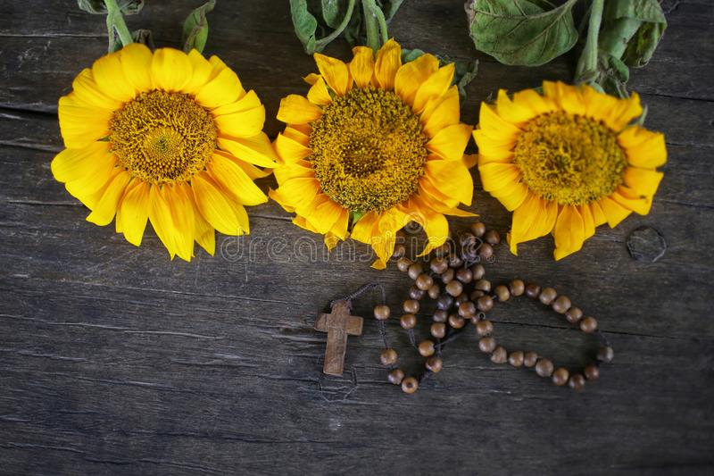 Wooden Rosary with Jesus Christ Cross Crucifix and three beautiful sunflwoers blossom arrangement on rustic table background. royalty free stock photos