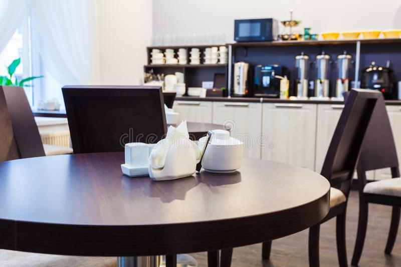 Wooden round table and sugar bowl, napkins, salt and pepper in modern cafe with furniture of kitchen on the background. Interior. royalty free stock photos