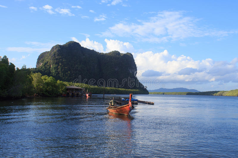 Wooden rowing boat on blue sea water and sun light reflect. Nature landscape at Trang Thailand stock photo