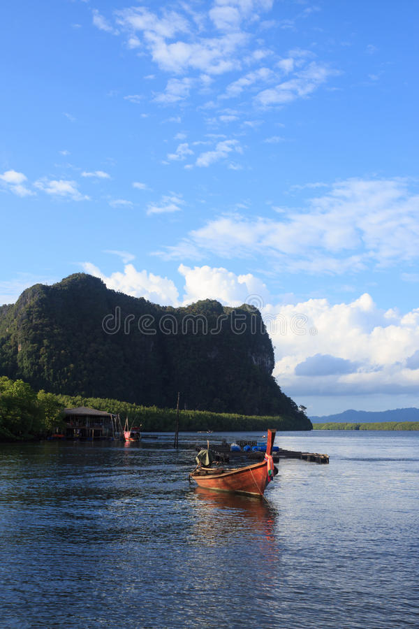 Wooden rowing boat on blue sea water and sun light reflect. Nature landscape at Trang Thailand stock photography