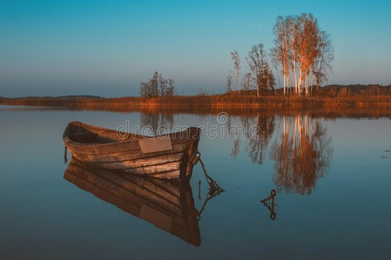 Wooden boat with reflection in a still lake water at twilight on autumn landscape. Wooden rowing boat with reflection in a still lake water at twilight on autumn royalty free stock images