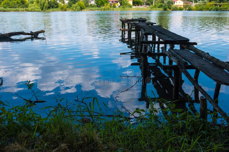 Wooden ruined old pier on the river bank. Old ruined wooden pier and clouds reflected in the river stock photos