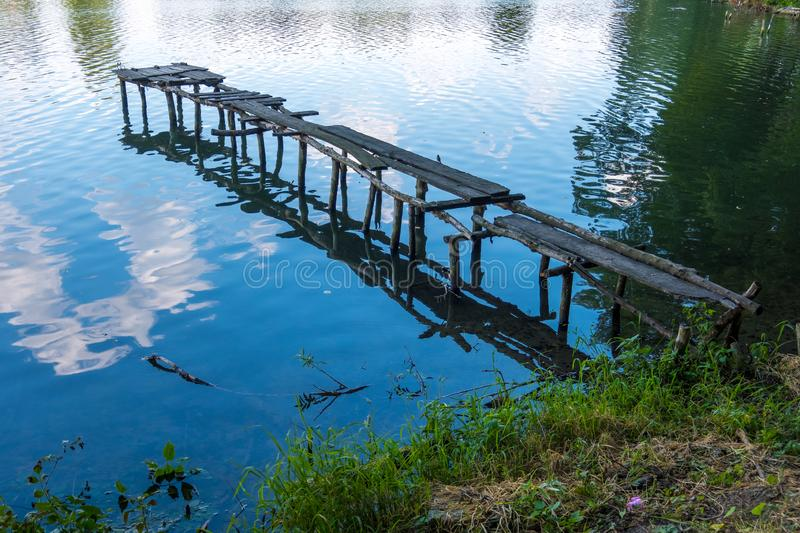 Wooden ruined old pier on the river bank. Old ruined wooden pier and clouds reflected in the river stock images