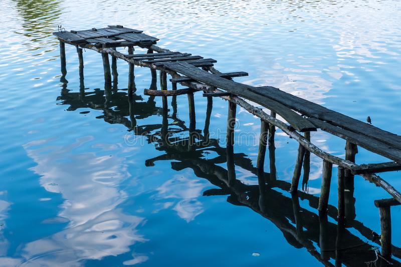 Wooden ruined old pier on the river bank. Old ruined wooden pier and clouds reflected in the river stock image