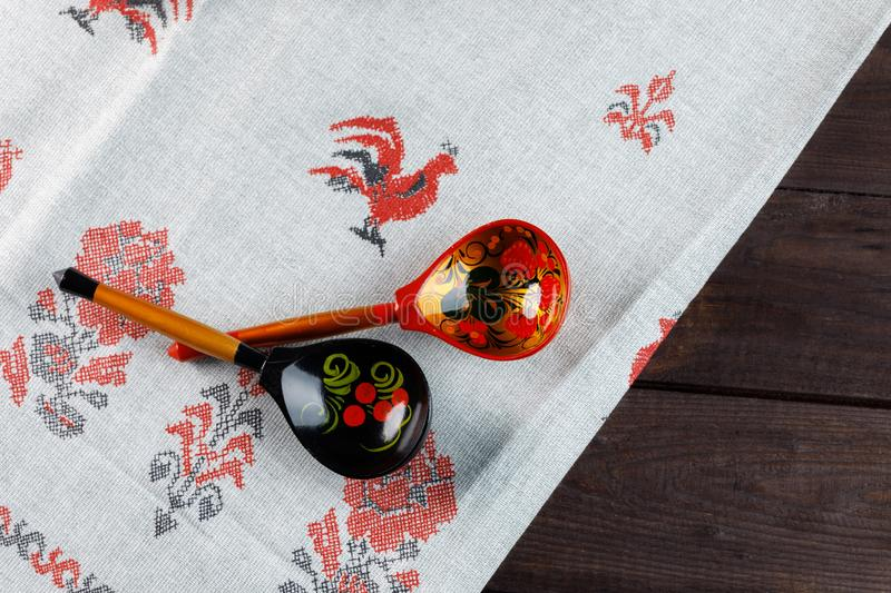 Wooden Russian hand-painted spoons and tablecloth with a traditional pattern on natural wooden background stock photos
