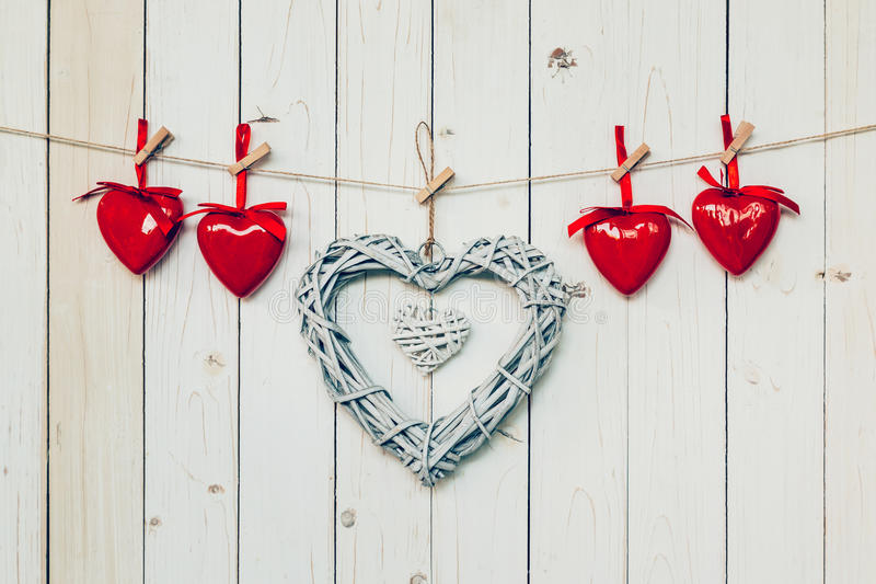 wooden rustic decorative hearts hanging on vintage wooden background with space. stock photo