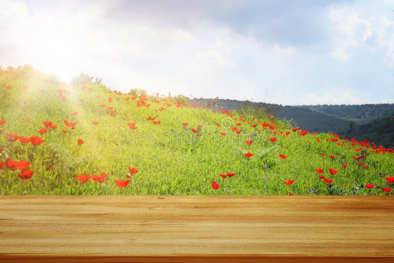 Wooden rustic table in front of field red poppies. product display and picnic concept. Wooden rustic table in front of field red poppies. product display and stock images