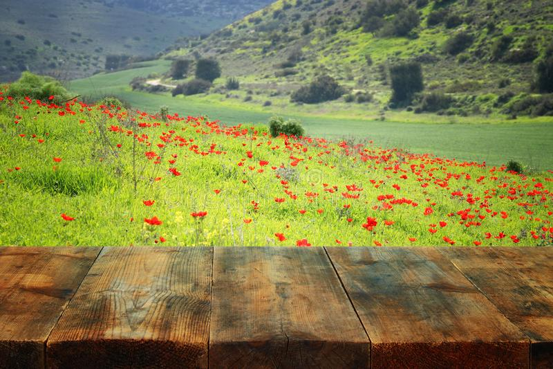 Wooden rustic table in front of field red poppies. product display and picnic concept. Wooden rustic table in front of field red poppies. product display and stock image